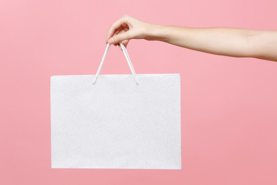 Close up female holds in hand white clear empty blank craft paper gift bag for purchases after shopping isolated on pastel pink background. Packaging template mockup. Delivery concept advertising area