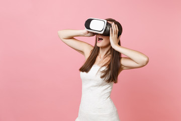 Portrait of amazed bride woman in white wedding dress, headset of virtual reality clinging to head isolated on pastel pink background. Organization of wedding concept. Copy space for advertisement.