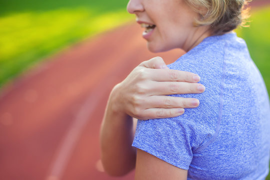 Back view of athletic young woman in sportswear touching her painful neck at the stadium. Sport, health and people concept