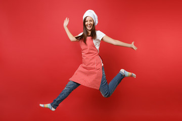 Housewife female chef cook or baker in striped apron white t-shirt, toque chefs hat isolated on red wall background. Full length portrait housekeeper woman jumping high up. Mock up copy space concept.