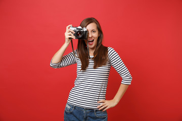 Portrait of cheerful young woman in striped clothes taking picture on retro vintage photo camera isolated on bright red wall background. People sincere emotions, lifestyle concept. Mock up copy space.