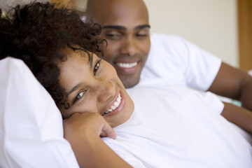 Young couple lying bed at home smiling at camera