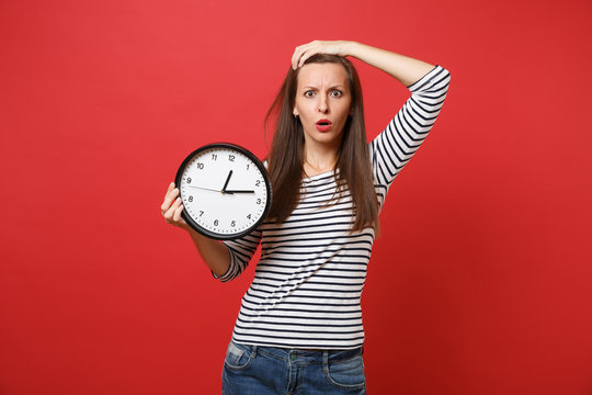 Shocked puzzled young woman in striped clothes putting hand on head holding round clock isolated on red background. Time is running out. People sincere emotions, lifestyle concept. Mock up copy space.