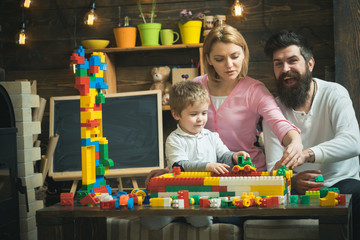 Playroom concept. Little child play with toy bricks in playroom. Son with mother and father build structure model in playroom. Having fun in playroom