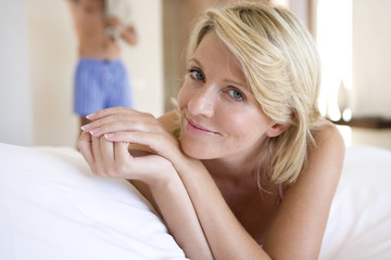 Portrait of mature woman in pajamas lying on bed at home