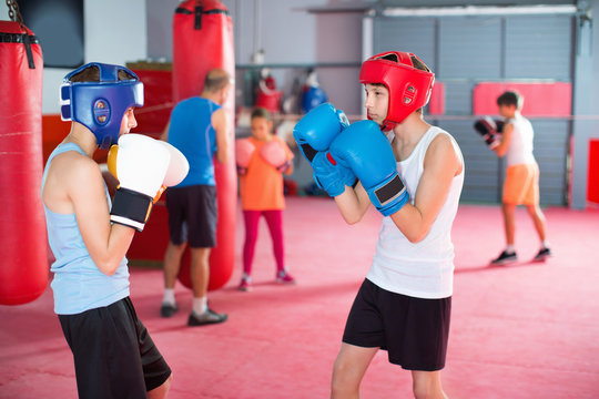 Two young boxer wearing gloves and helmet sparring