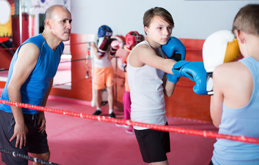 Teenage sportsman at boxing workout with instructor