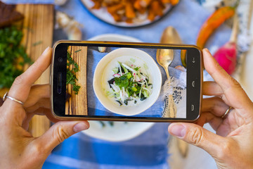 Smartphone photography of food. Woman hands holds mobile phone and take or make beautiful trendy food photo for social networks or blogging. Okroshka russian traditional cold soup