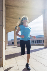 Low angle view of female athlete running on footpath in city during sunny day