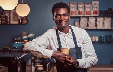 African barista smiling at camera relaxing after workday with coffee while leaning on the counter at coffee shop.