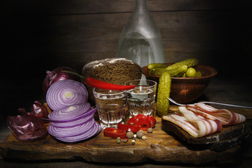 Vodka and snack to it on a wooden background.
