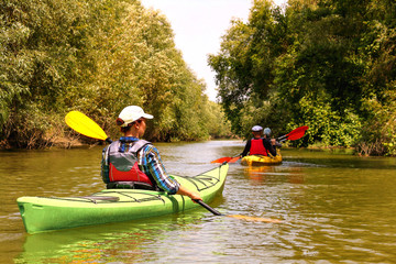 Group of people (friends) kayaking in Danube river near thickets of wild grapes