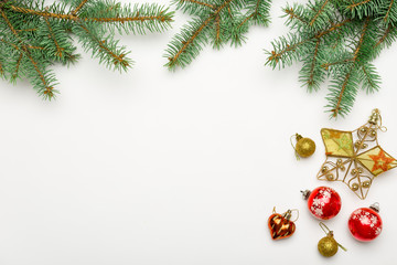 Holiday frame of Christmas decorations on white background with fir branch, gold and red balls, stars. Elegant New Year`s snowy card. Top view. Flat lay.