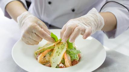 Chef preparing Caesar salad with shrimps