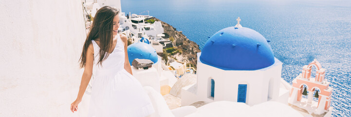 Fototapete - Santorini travel tourist woman on vacation in Oia walking on stairs visiting the famous white village with the mediterranean sea and blue domes. Europe summer destination panoramic banner.