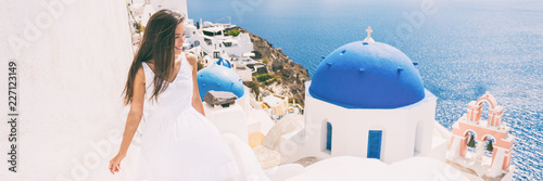 Wall mural Santorini travel tourist woman on vacation in Oia walking on stairs visiting the famous white village with the mediterranean sea and blue domes. Europe summer destination panoramic banner.