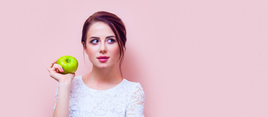 portrait of a beautiful young woman with a green apple standing on the pink background