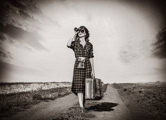 Beautiful girl in plaid dress with bag and binocular on countryside. Image in black and white color style