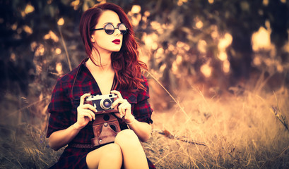 Beautiful girl in plaid dress retro camera and sunglasses at countryside