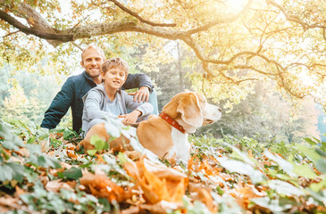 Wall Mural - Father, son and beagle dog walk in autumn park, warm indian summer day