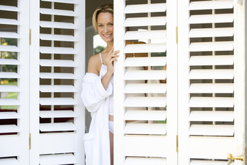 Woman in bathrobe and underwear looking out of shutters at camera