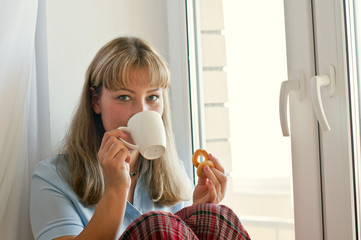 girl with a cup of tea or coffee by the window with a blanket, autumn or winter concept. Relaxation