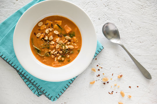 Peanut stew in a white bowl with blue napkin