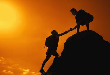 Mann auf dem Gipfel reicht Freund die Hand
