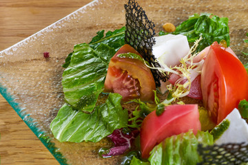 Fresh vegetable salad with fresh tomatoes, lettuce and arugula. Top view of fresh salad on glass plate on wooden table.