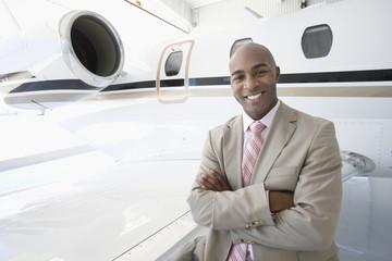 Businessman on trip with executive jet aeroplane in hangar