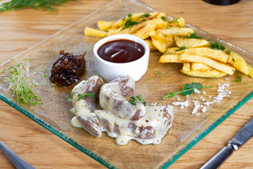 French fries with grilled veal served with sauce on glass plate. Delicious potato with meat in sauce on wooden table.