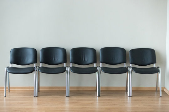 Row of black office chairs standing in corridor or conference room, empty dark seats arranged in line in boardroom, range of basic stools in front of white wall. Interview, recruitment concept
