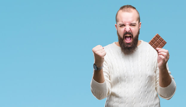 Young hipster man eating chocolate bar over isolated background annoyed and frustrated shouting with anger, crazy and yelling with raised hand, anger concept