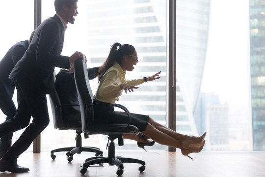 Laughing diverse work team play funny game in office, excited employees engaged in riding on chairs competition, multiethnic smiling workers entertain at workplace enjoying creative teamwork activity