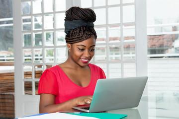 Afrikanische Frau arbeitet am Laptop