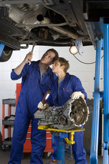Mechanics with car engine part in auto repair garage