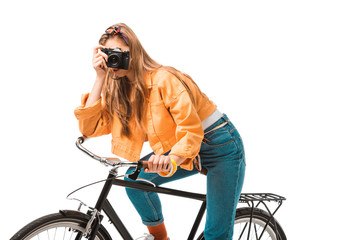 young attractive hipster girl sitting on bicycle and shooting on camera isolated on white