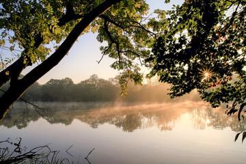 romantischer Fluss am Morgen im Dunst mit Sonnenstrahlen