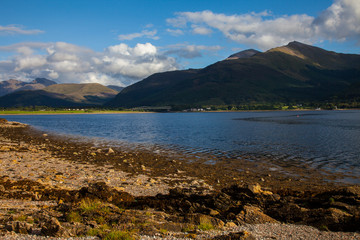 Colorful Scottish landscape with a sunny summer day, blue waves in reservoir, white clouds on the blue sky and over the green mountains and a sandy brown shore with stones