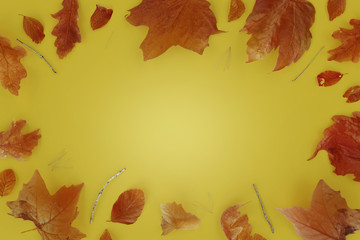 autumn leaf laying on yellow background with an empty middle spot