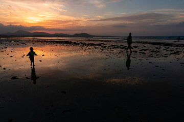 silhouettes of dad and son at sunset on the ocean at low tide