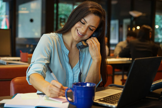 Businesswoman talking on telephone while working in office