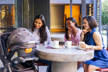 Smiling female friends looking at stroller in coffee shop