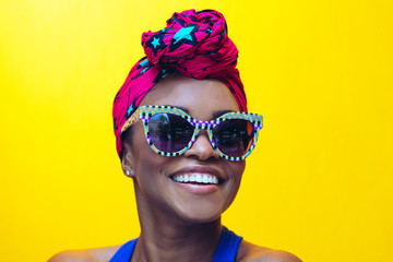 Close up of a smiling woman with sunglasses against yellow background