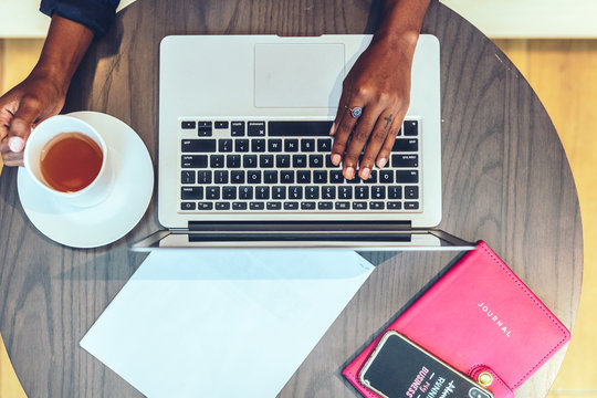 Overhead view of businesswoman's hands working on laptop in office