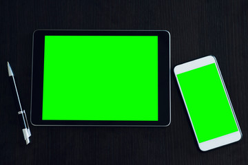 Top view business flat lay with two gadgets black tablet computer and white smartphone with green screen and pen on black table. Chroma key
