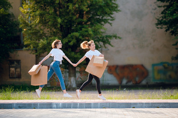 Two young happy female friends in casual clothes with shopping bags running on the street holding hands.