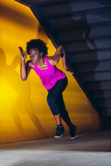 Athlete woman running by yellow wall