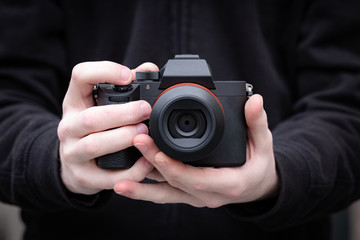Mirrorless digital camera in hand of a young man. Clean image with no brands or signs