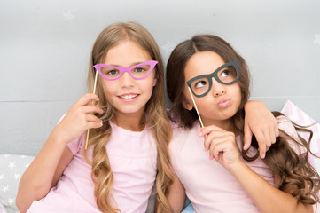 Girls children posing with grimaces photo booth props. Pajamas party concept. Girls friends having fun pajamas party. Friends cheerful posing with eyeglasses accessories for party. Playful mood